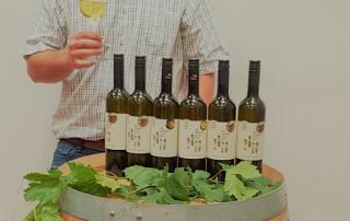 Kellermeister freut sich über seine Weinprämierungen
